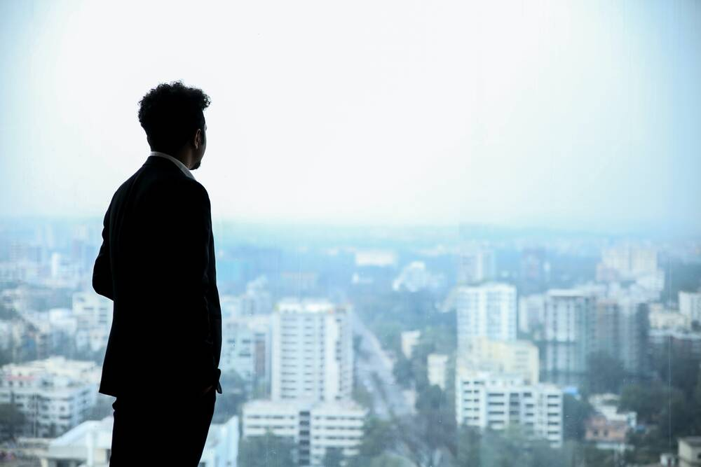 A businessman in an office building looking at the city though the window