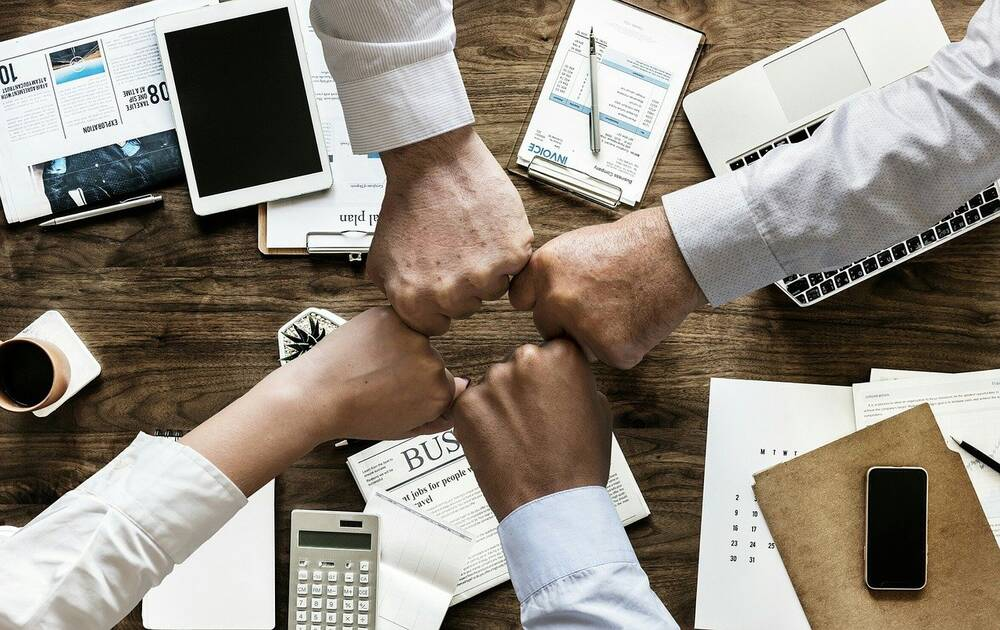 Four business people joining hands