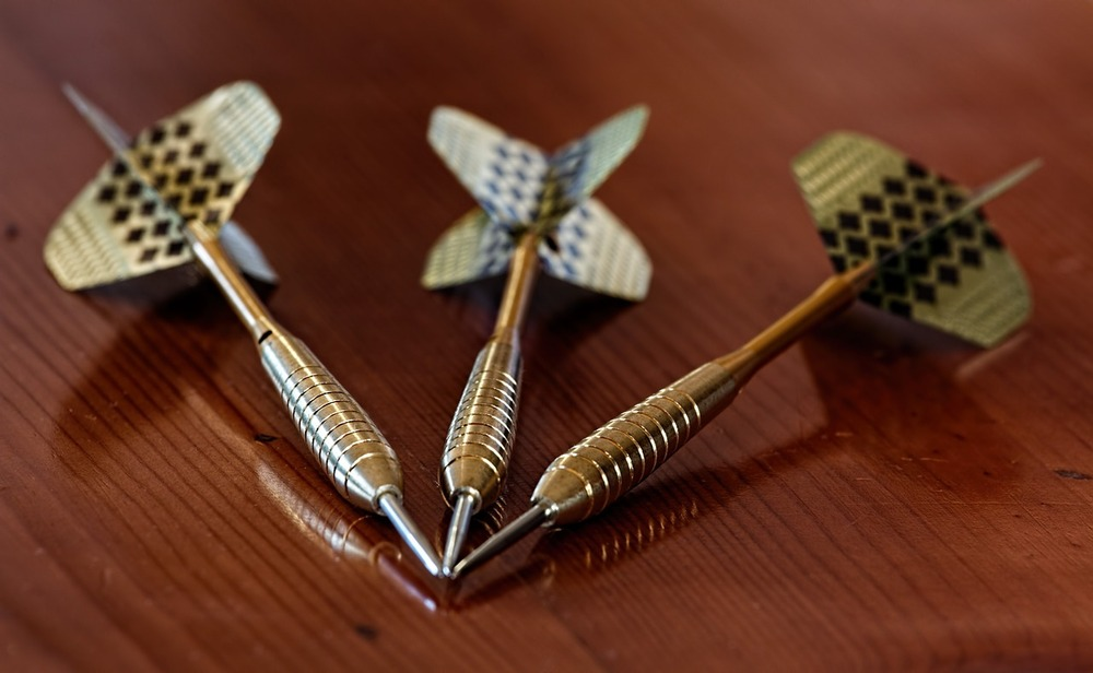 Three darts laying on a table